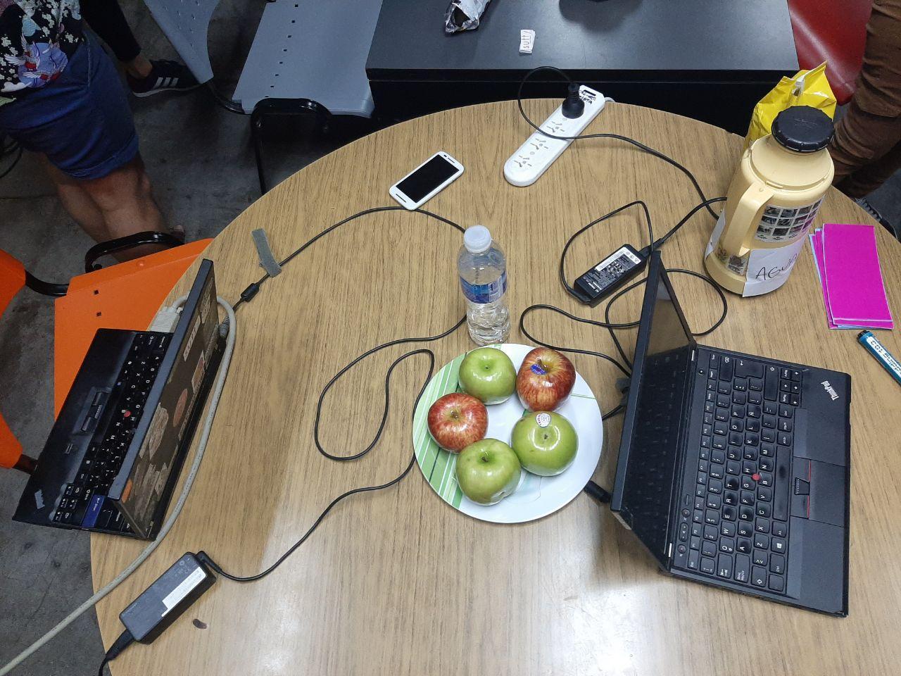 Fruta, agua, agua para el mate y dispositivos para escribir: celu, compus y cartulinas